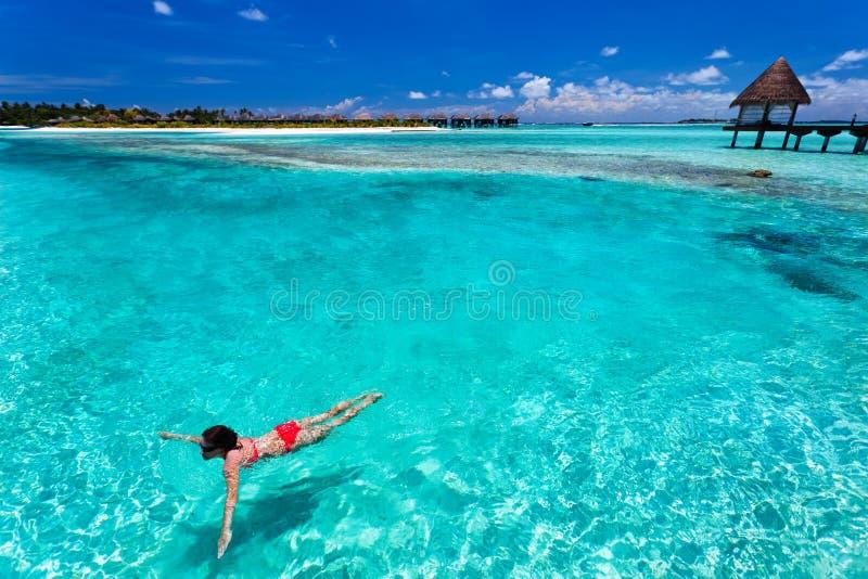 Frau in der roten Bikinischwimmen in einer korallenroten Lagune lizenzfreie stockfotografie