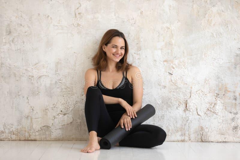 Frau in der schwarzen Sportkleidungsholding-Mattenentspannung gelehnt an der Wand stockbilder