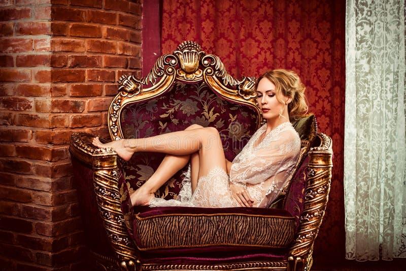 Frau in der Spitzerobe sitzt in einem antiken Lehnsessel stockfotografie