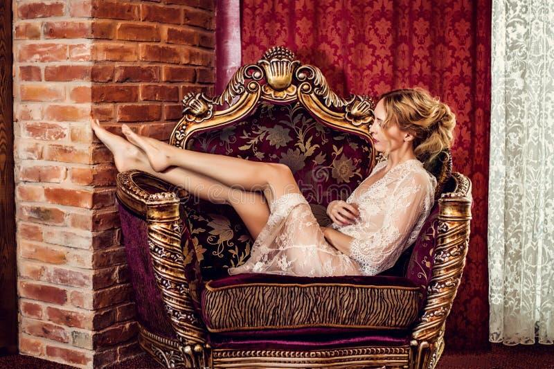 Frau in der Spitzerobe sitzt in einem antiken Lehnsessel stockfotos