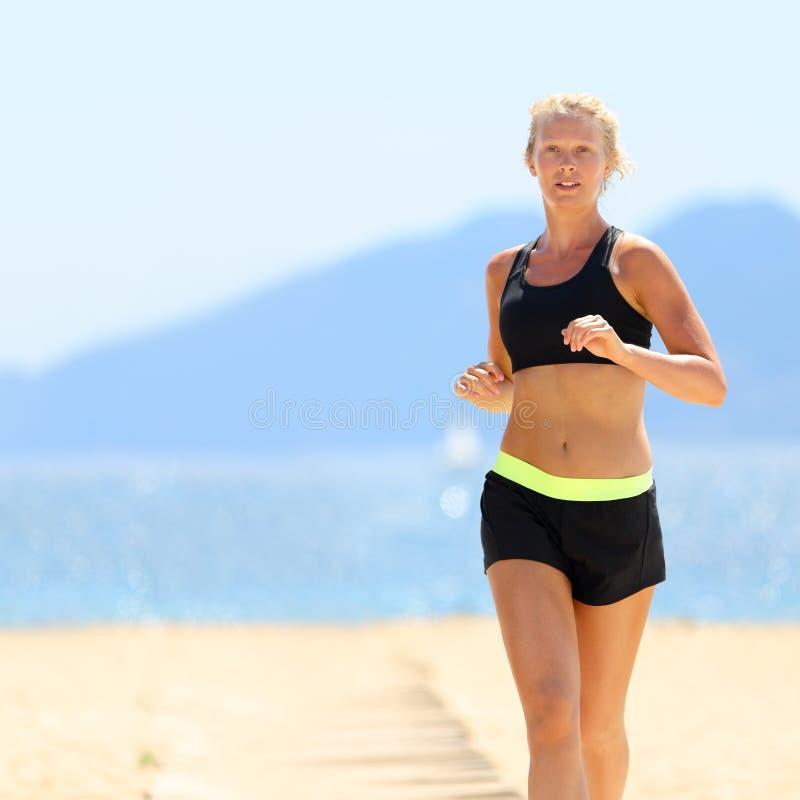 Frau in der Sportkleidung, die am Strand läuft stockfoto