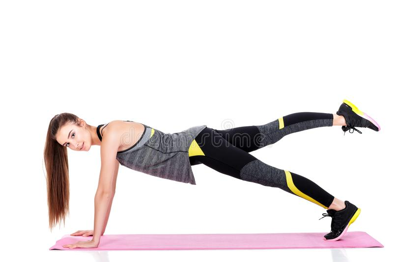 Frau in der Sportkleidung tut Übungen auf Eignung Matte stockfoto