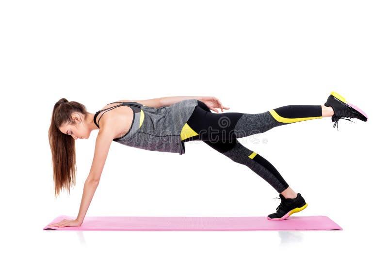 Frau in der Sportkleidung tut Übungen auf Eignung Matte lizenzfreie stockbilder