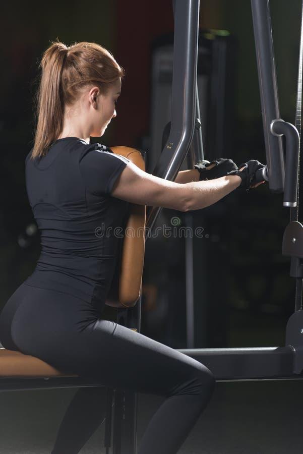 Frau an der Sportturnhalle, die Armübungen auf einer Maschine tut stockbilder