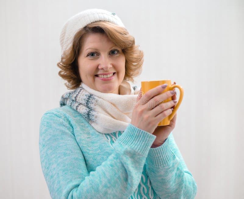 Frau in der Strickjacke, in Hut und in Schal, die gelbe Tasse Tee halten lizenzfreie stockfotos