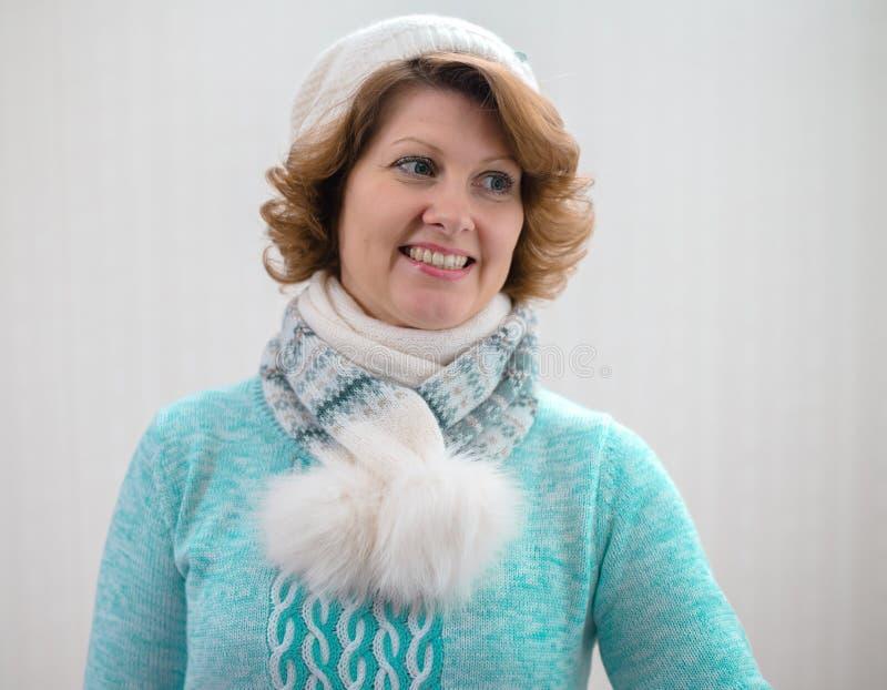 Frau in der Strickjacke, im Hut und im Schal auf weißem Hintergrund lizenzfreie stockbilder