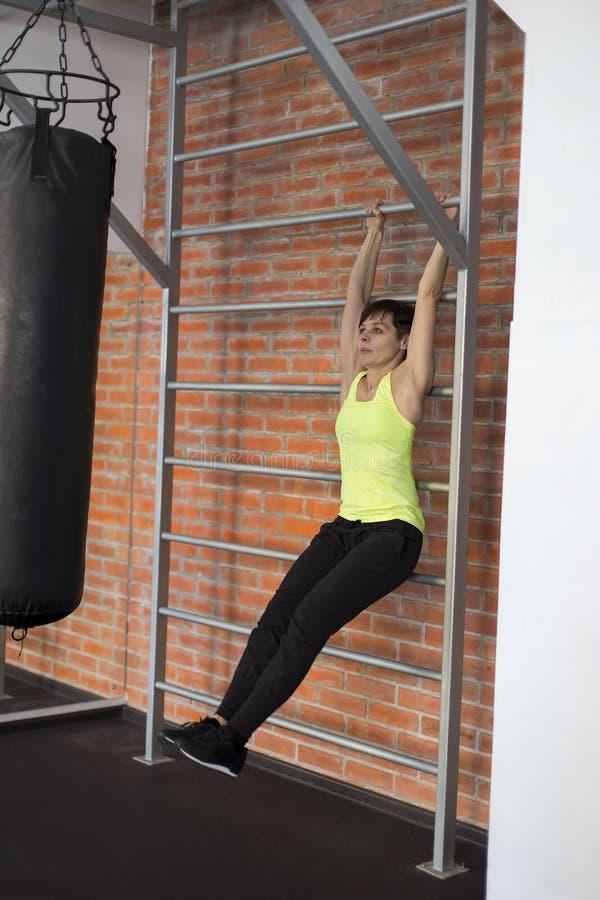 Frau an der Turnhalle, die Übungen die Beine zur Spitze tut lizenzfreie stockbilder