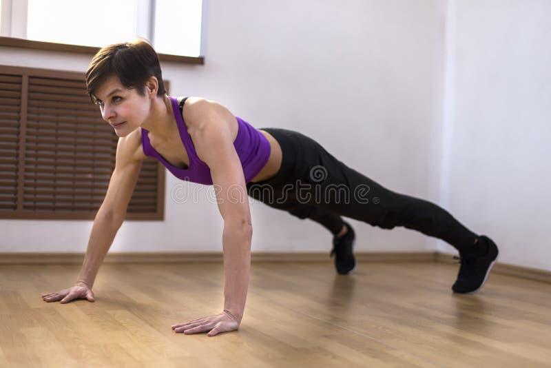 Frau an der Turnhalle, die Übungen tut stockbild