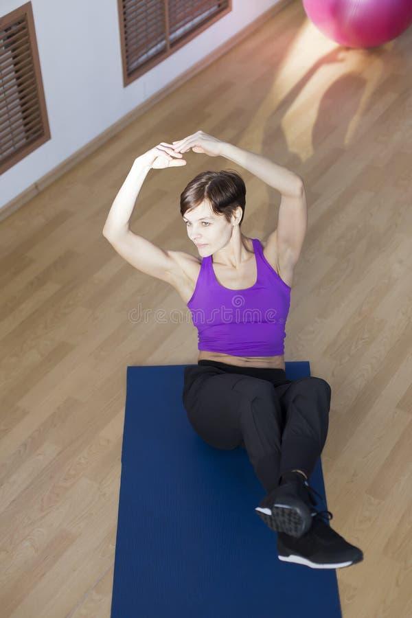 Frau an der Turnhalle, die Übungen tut stockfoto