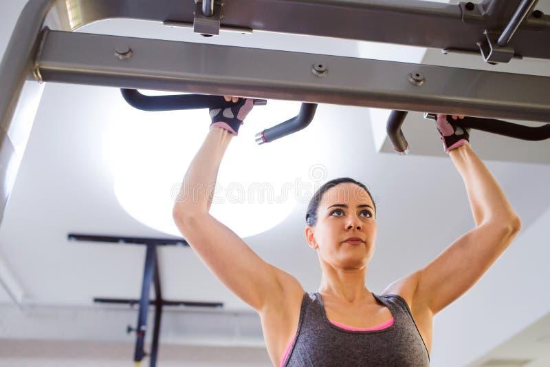 Frau in der Turnhalle, die Armübungen auf einer Maschine tut lizenzfreie stockfotos