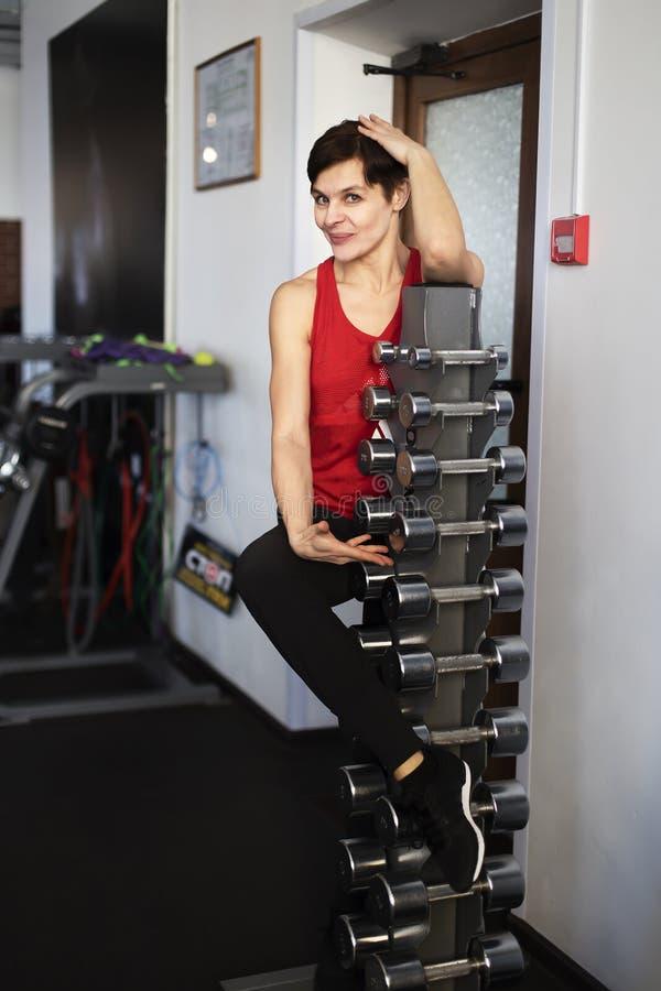 Frau in der Turnhalle, mit Gewichten stockbild