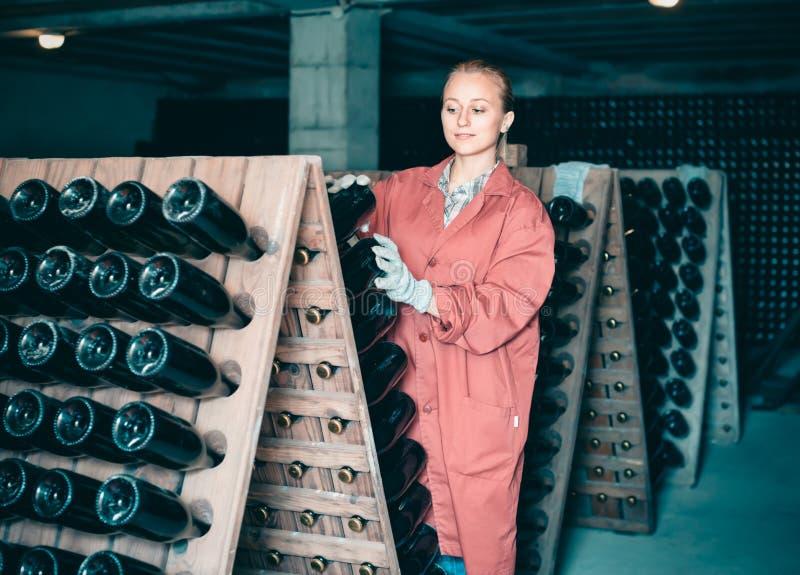 Frau in der Uniform, die mit Flaschenspeicher arbeitet, beansprucht in der Weinkellerei cel stark stockfotografie