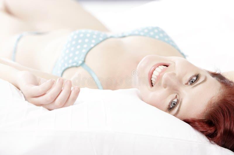 Frau in der Unterwäsche auf Bett lizenzfreie stockfotografie