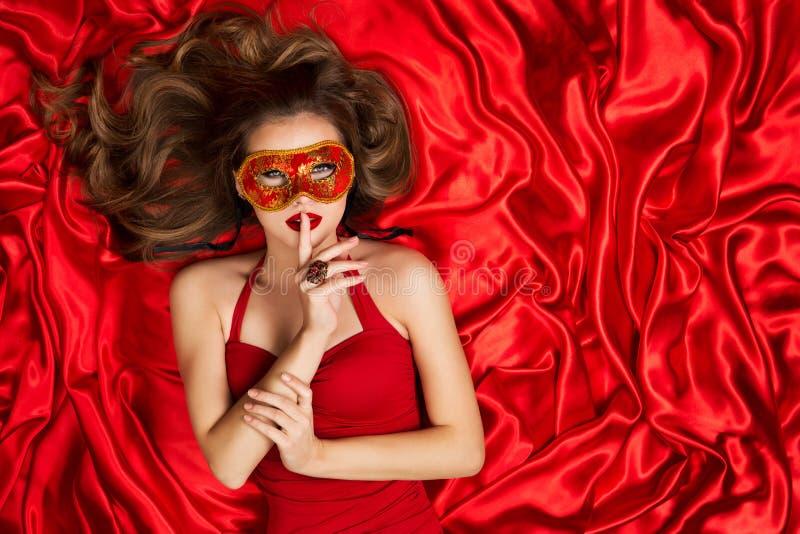 Frau in der venetianischen Maske, die auf rotem Seidengewebe-Hintergrund, Mode-Modell Finger auf Lippen liegt stockfotografie
