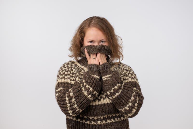 Frau in der warmen braunen Strickjacke, die ihr Gesicht versteckt Nur Augen werden gesehen Sie möchte Anonymus bleiben lizenzfreie stockfotografie