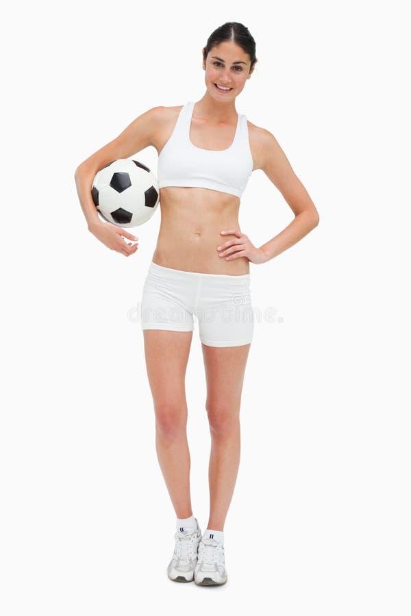Frau in der weißen Kleidung, die eine Fußballkugel anhält lizenzfreies stockbild