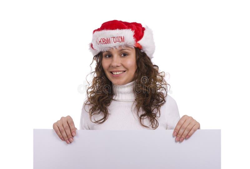 Frau in der Weihnachtsschutzkappe, die unbelegtes informatorisches anhält lizenzfreies stockbild