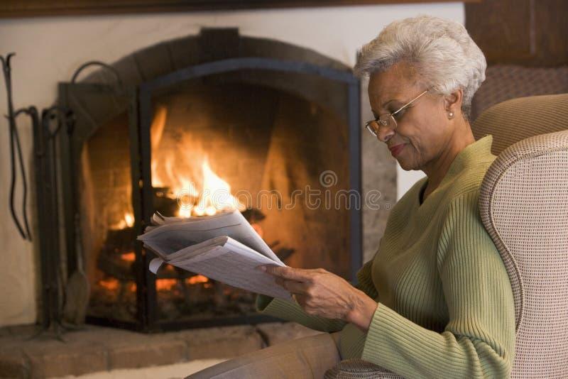 Frau in der Wohnzimmerlesezeitung lizenzfreie stockfotos