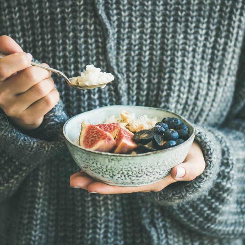 Frau in der woolen Strickjacke Reiskokosnussbrei, quadratische Ernte essend stockfotos