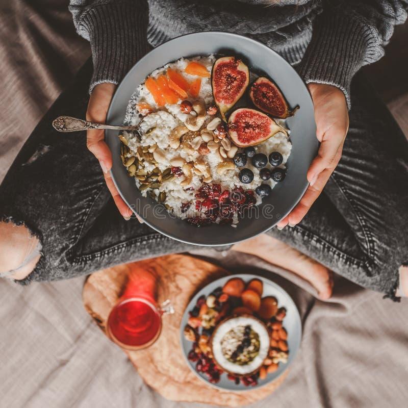 Frau in der woolen Strickjacke und in den Jeans Reis-Kokosnussbrei des strengen Vegetariers mit Feigen, Beeren, Nüsse essend stockfoto
