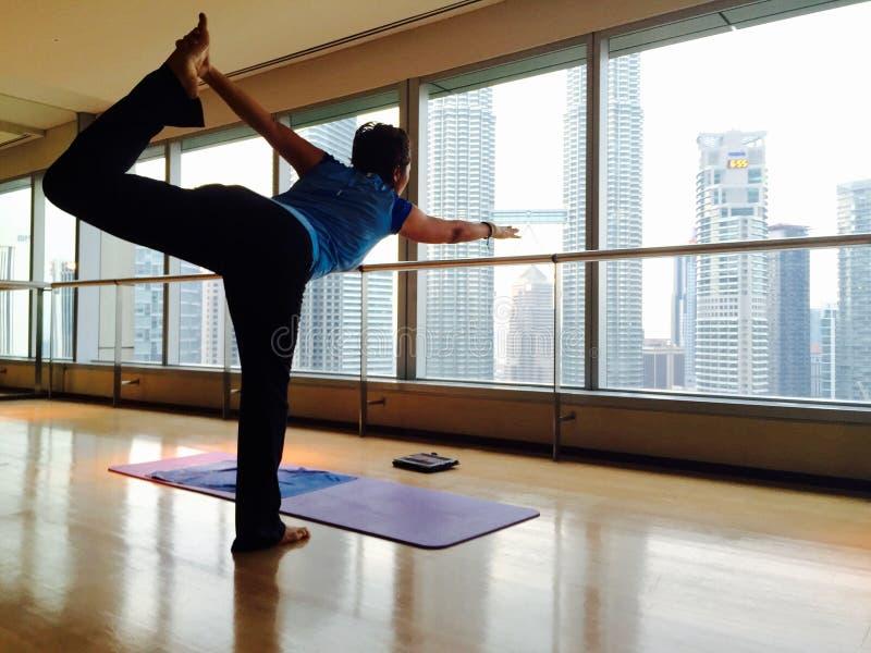 Frau in der Yogahaltung durch Fenster lizenzfreies stockfoto