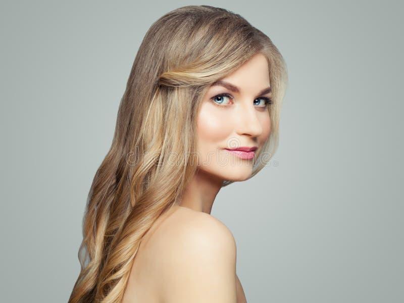 Frau des blonden Haares mit gelockter Frisur und klarer Haut Gesichtsbehandlungs-, Haarpflege- und Cosmetologykonzept lizenzfreies stockfoto