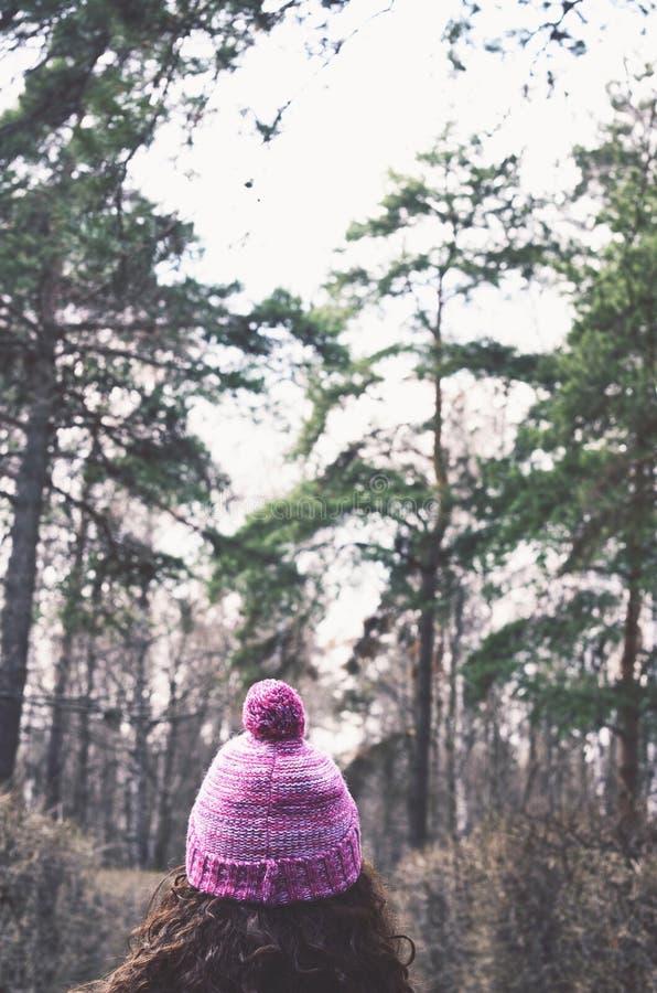 Frau des gelockten Haares in der Strickmütze im Herbstwald stockfoto