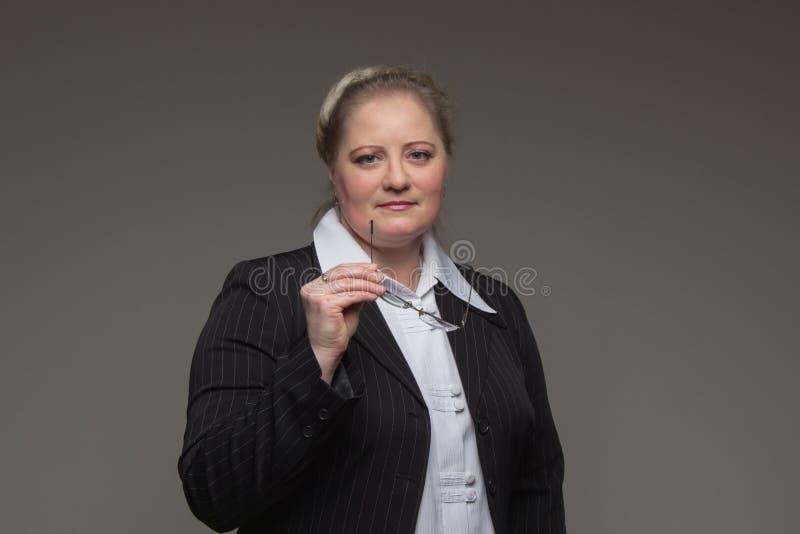 Frau des Geschäfts von mittlerem Alter mit Gläsern im schwarzen Anzug lizenzfreies stockbild