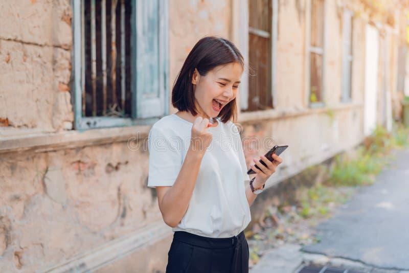Frau des glücklichen lächelnden und haltenen intelligenten Telefons mit überrascht für Erfolg lizenzfreie stockfotografie