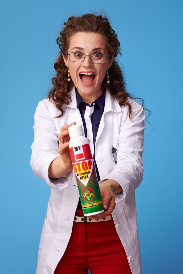 Frau des praktischen Arztes, die Insektenvertilgungsmittel auf Blau zeigt stockbild
