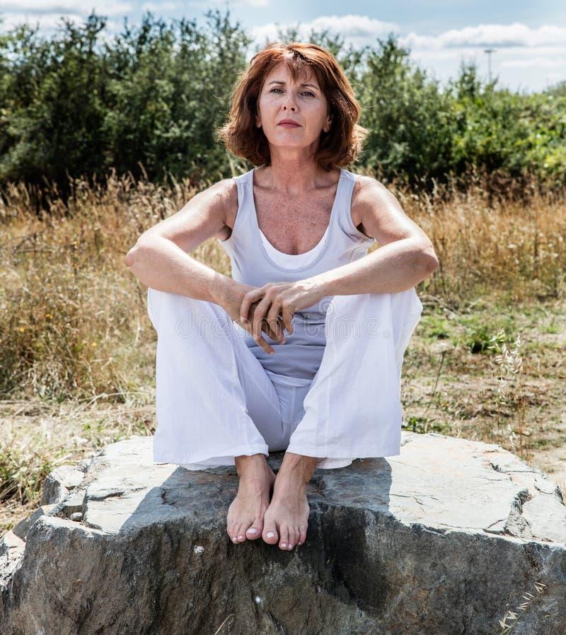 Frau des Yoga 50s, die auf der Steinentspannung für geistigen Frieden sitzt lizenzfreie stockfotos