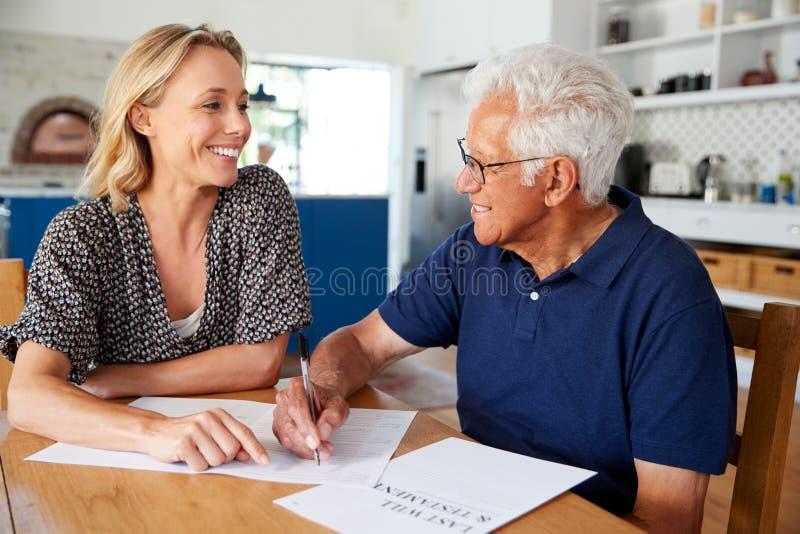 Frau, die älterem Mann hilft, Testament zu Hause abzuschließen lizenzfreie stockbilder