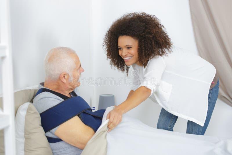 Frau, die älteren Mann im Pflegeheim mach's gut ist stockbild