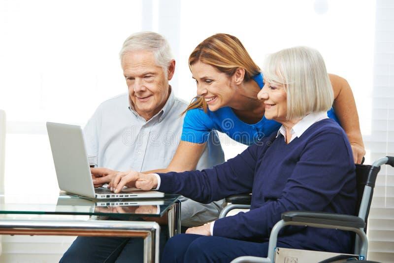 Frau, die älteren Paaren mit Computer hilft stockfotos