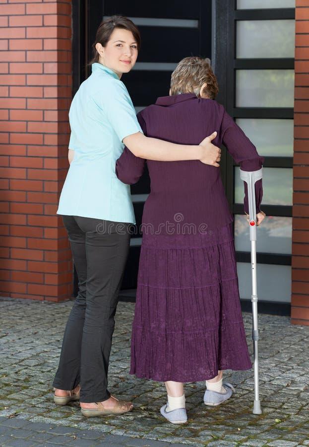 Frau, die älterer Dame auf Krücken hilft, Haus zu betreten stockfotos