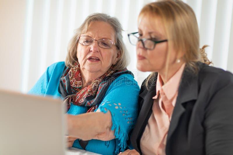 Frau, die älterer erwachsener Dame auf Laptop-Computer hilft lizenzfreies stockbild