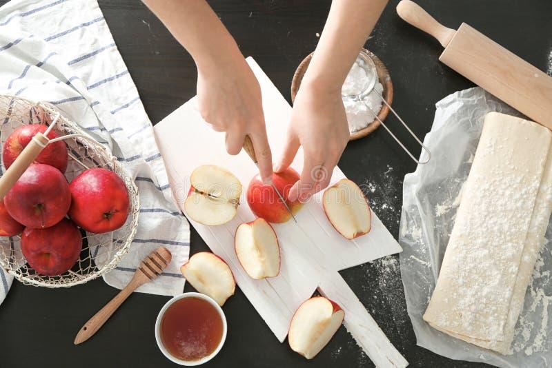Frau, die Äpfel für Gebäck auf hölzernem Brett schneidet stockfotografie