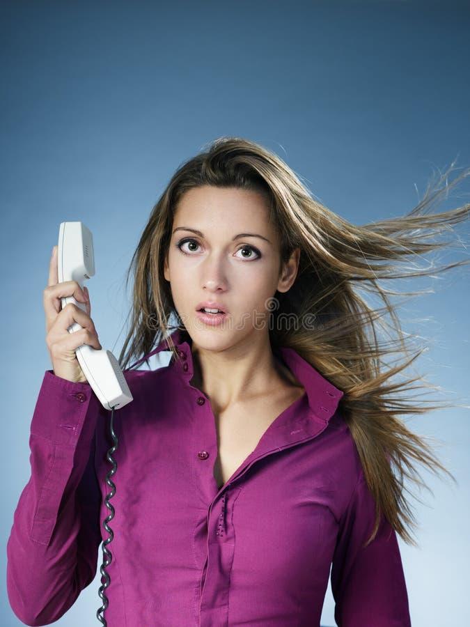 Frau, die über dem Telefon gekreischt wird lizenzfreies stockfoto