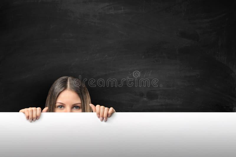 Frau, die über den Rand der leeren leeren Papieranschlagtafel mit Kopienraum späht lizenzfreie stockbilder