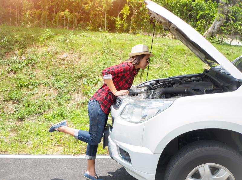 Frau, die über der Prüfung ihres Automotors nach der Aufgliederung sich lehnt lizenzfreies stockbild