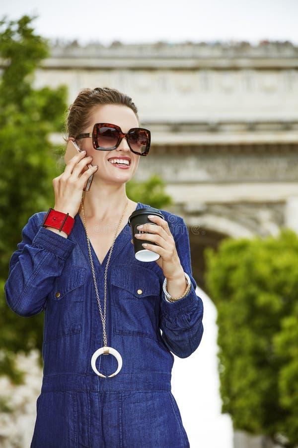 Frau, die über einen Smartphone beim Trinken des Kaffees in Paris spricht lizenzfreies stockbild