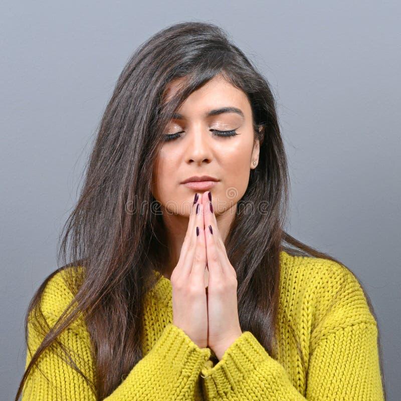 Frau, die über etwas betet oder um Gnade gegen grauen Hintergrund bittet lizenzfreies stockfoto