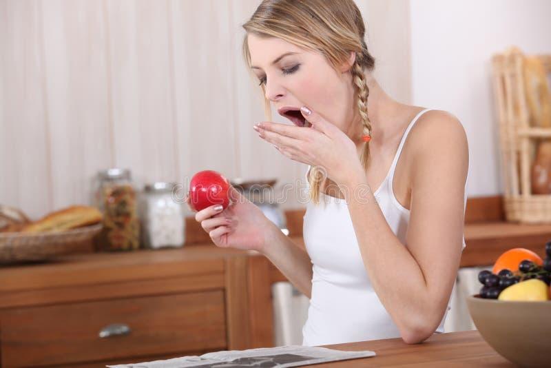 Frau, die über Frühstück gähnt stockbilder