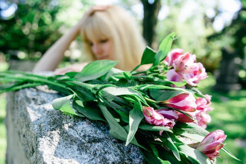 Frau, die über Grab sich Sorgen macht lizenzfreies stockbild