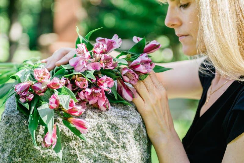 Frau, die über Grab sich Sorgen macht lizenzfreies stockfoto