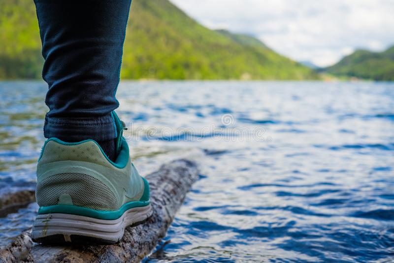 Frau, die ?ber Holz im tiefen blauen Wasser im Alpen eingelassenen Bayern balanciert lizenzfreies stockfoto