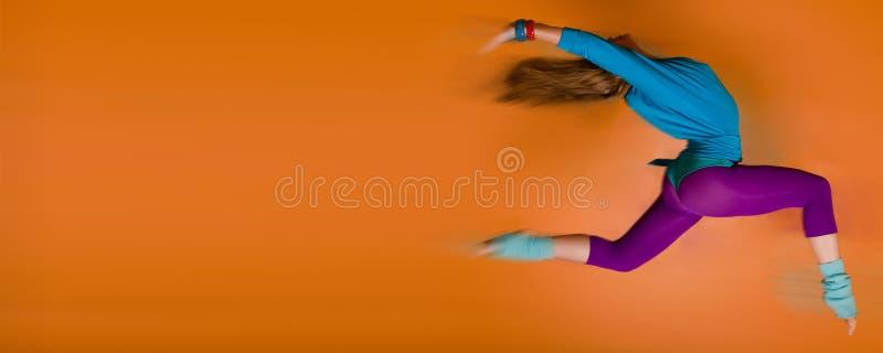 Frau, die über orange Hintergrund springt stockbilder