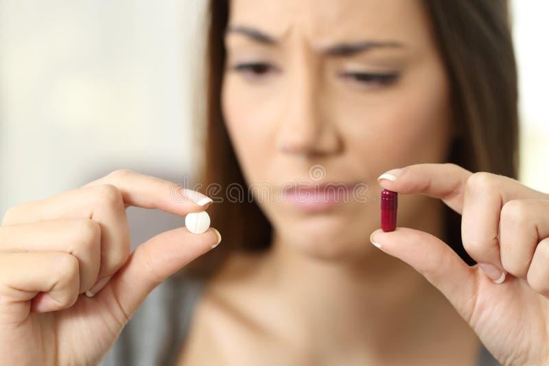 Frau, die über Pille oder Kapsel sich wundert lizenzfreie stockfotografie