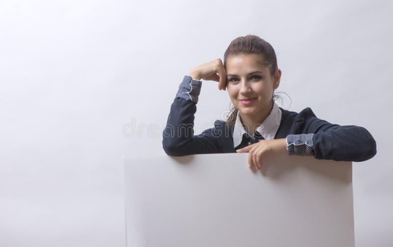 Frau, die über Rand der leeren leeren Papieranschlagtafel mit Kopienraum für Text späht stockfoto