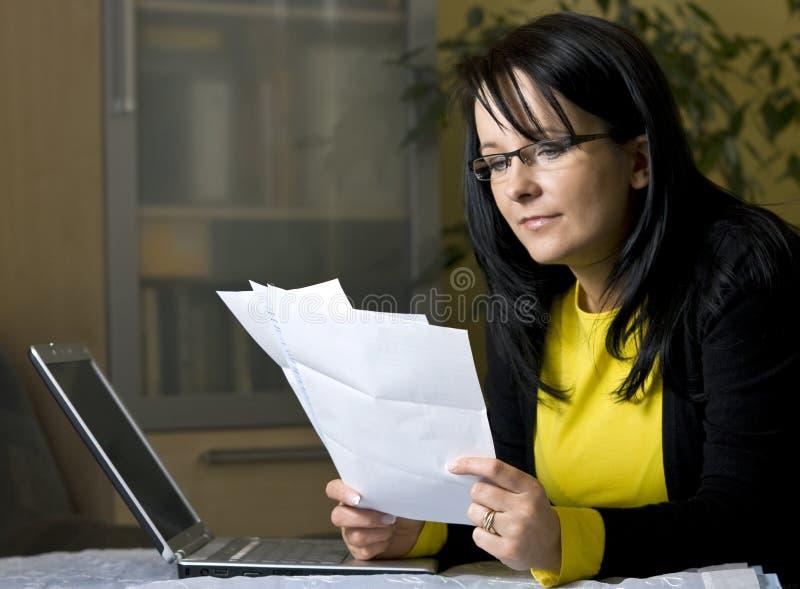 Frau, die über Schreibarbeit schaut lizenzfreie stockbilder